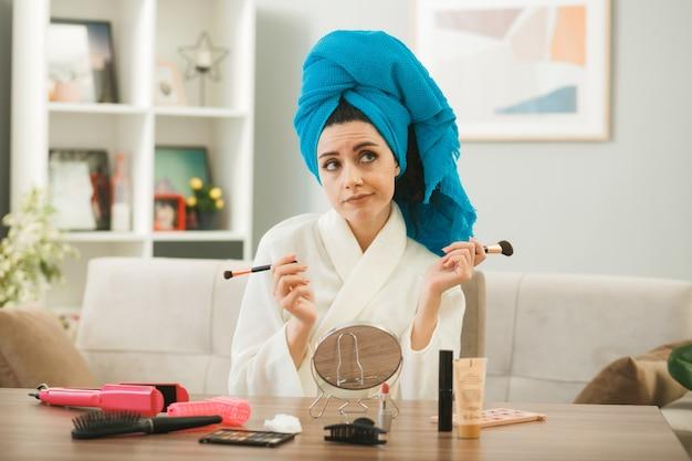 Denkend aan de kant kijkend jong meisje met make-upborstel zittend aan tafel met make-uptools in de woonkamer
