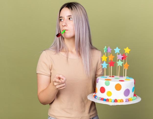 Denkend aan de kant kijkend jong mooi meisje met taart blazend feestfluitje dat je gebaar laat zien