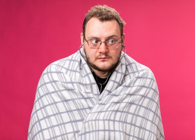 Denkend aan de kant van een zieke man van middelbare leeftijd die een stethoscoop draagt gewikkeld in een plaid geïsoleerd op een roze muur