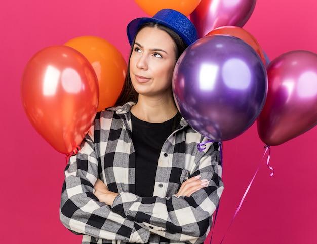 Denkend aan het opzoeken van jonge mooie vrouw met een feesthoed die vooraan staat met ballonnen die handen kruisen geïsoleerd op roze muur