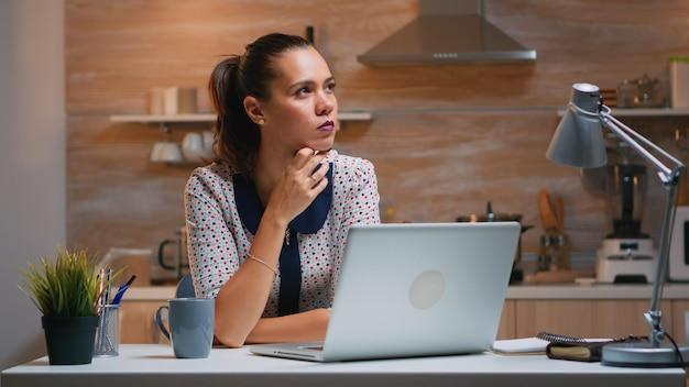 Denkend aan het volgende project terwijl je op afstand werkt vanuit huis, de taken lezend met een laptop in de keuken. drukke gefocuste werknemer die moderne technologienetwerk draadloos gebruikt om overuren te maken voor werk t