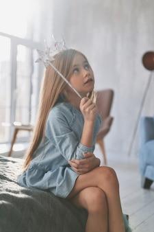 Denkend aan... schattig klein meisje dat met een toverstaf speelt terwijl ze thuis tijd doorbrengt