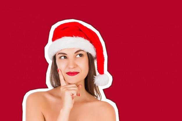 Denkend en reflecterend meisje in een kerstmuts. emotionele vrouw in rode kerstman hoed magazine collage stijl. gelukkig kerstmis en nieuwjaar vakantieconcept