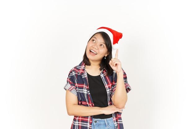Denkend gebaar van mooie aziatische vrouw met rood geruit overhemd en kerstmuts geïsoleerd op wit