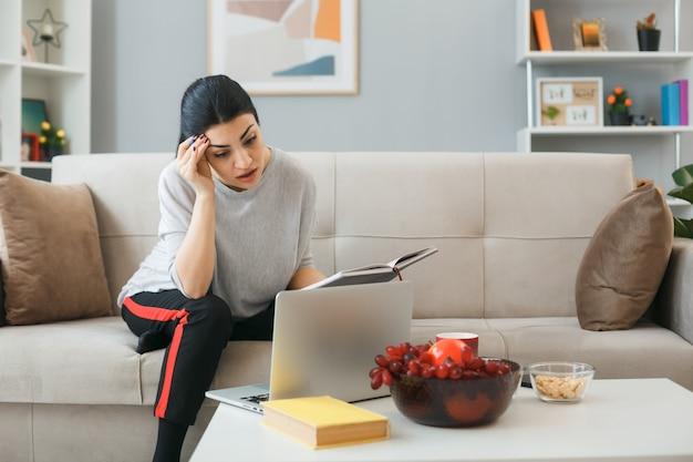 Denkend hand op voorhoofd zettend jong meisje gebruikte laptop met notitieboekje zittend op de bank achter de salontafel in de woonkamer