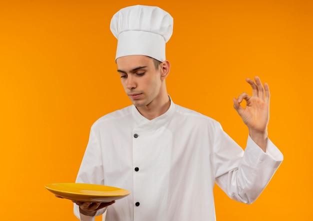 Denkend jong mannetje koel dragend plaat die van de chef-kok eenvormige holding ok gebaar met exemplaarruimte toont