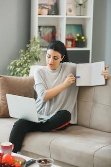 Denkend jong meisje gebruikte laptop vasthouden en wijst naar boek met pen zittend op de bank in de woonkamer