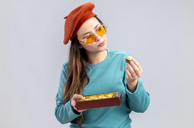 Denkend jong meisje op valentijnsdag met een hoed met een bril die een doos snoepjes vasthoudt en bekijkt die op een witte achtergrond wordt geïsoleerd