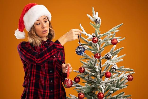 Denkend jong mooi meisje dat in de buurt van de kerstboom staat en een kerstmuts draagt, versier de kerstboom, versier de boom geïsoleerd op een oranje achtergrond
