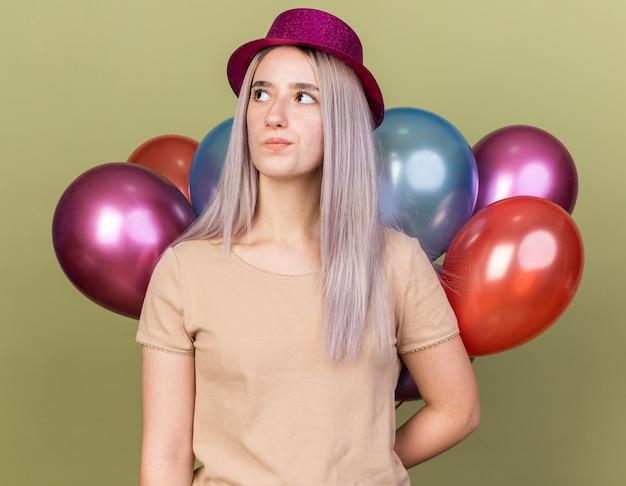 Denkend jong mooi meisje met feestmuts die achter ballonnen staat