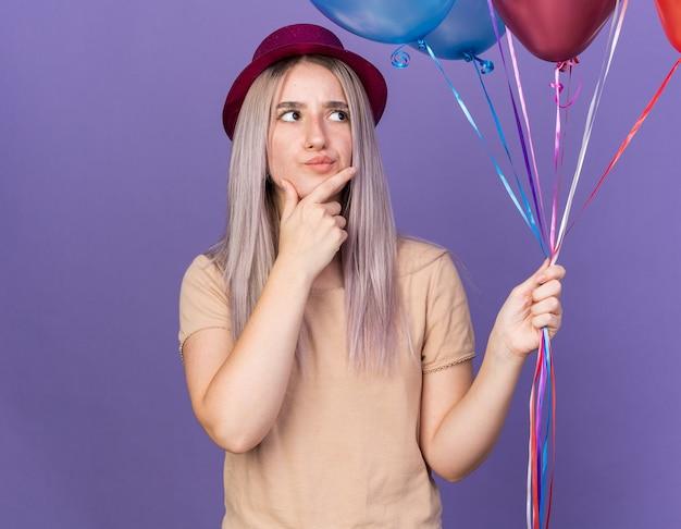 Denkend jong mooi meisje met feestmuts met ballonnen en greep bij de kin