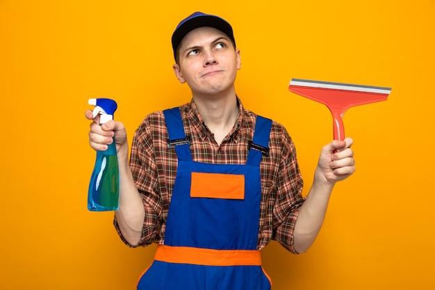 Denkend kijkend naar een jonge schoonmaakster met uniform en pet met schoonmaakmiddel met dweilkop