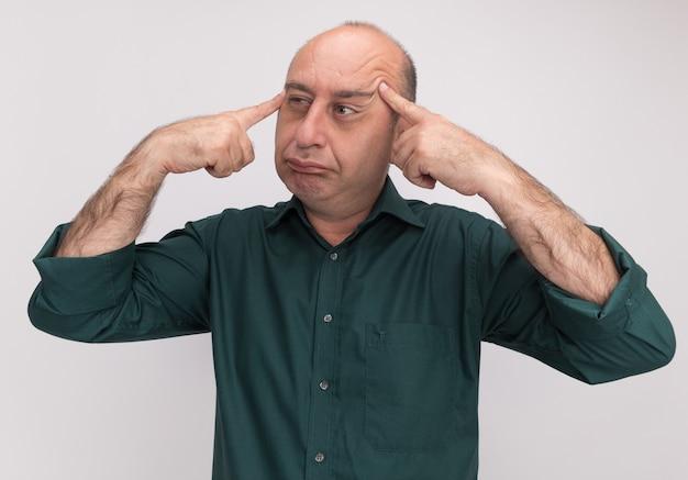 Denkend kijkend naar een man van middelbare leeftijd met een groen t-shirt die vingers op de tempel zet die op een witte muur is geïsoleerd