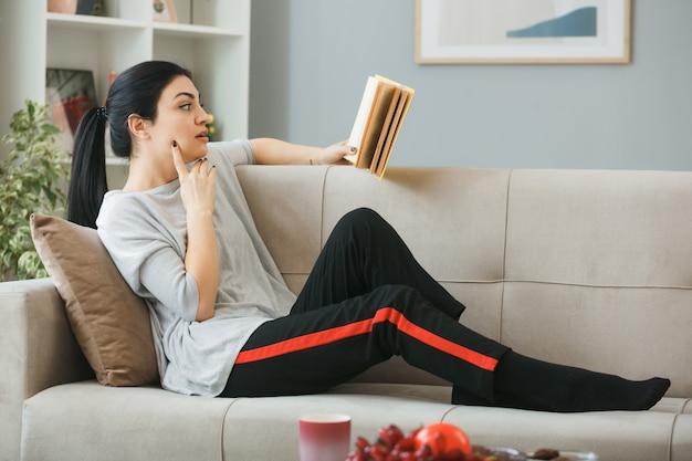 Denkend met de vinger op de wang van een jong meisje dat een boek leest dat op de bank achter de salontafel in de woonkamer ligt