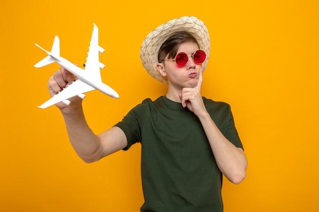 Denkend met de vinger op de wang van een jonge knappe kerel met een hoed met een bril die speelgoedvliegtuig vasthoudt