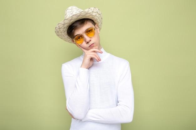 Denkend met de vinger op de wang van een jonge knappe kerel met een hoed met een bril?