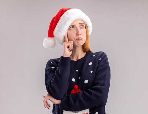 Denkend opzoeken van een jong mooi meisje met een kerstmuts die hand op de wang legt die op een witte muur wordt geïsoleerd
