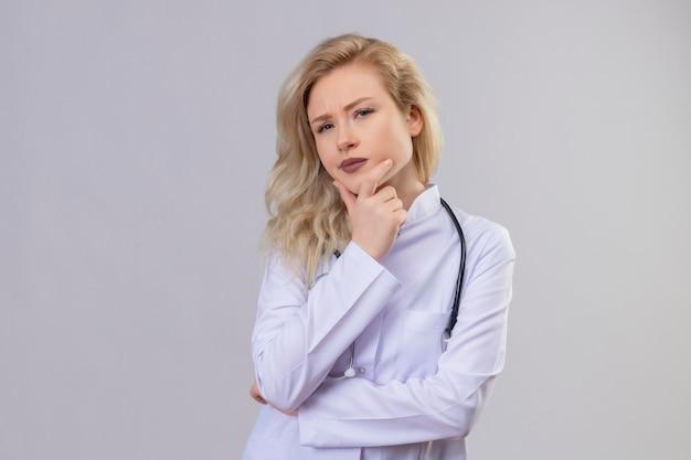 Denkende arts jong meisje met een stethoscoop in medische jurk greep kaak op witte achtergrond