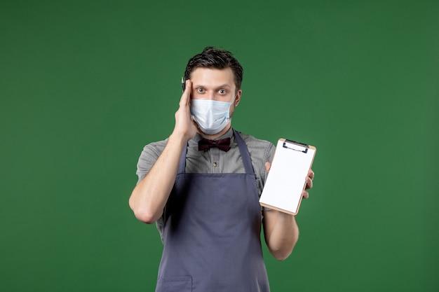 Denkende banketserver in uniform met medisch masker en chequeboekpen op groene achtergrond houden