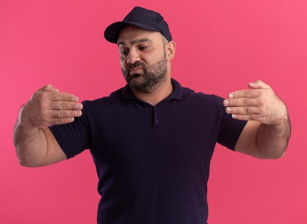 Denkende bezorger van middelbare leeftijd in uniform en pet die doet alsof hij iets vasthoudt dat op roze muur wordt geïsoleerd