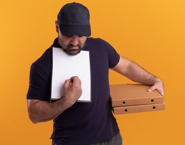 Denkende bezorger van middelbare leeftijd in uniform en pet die pizzadozen houdt en iets op klembord schrijft dat op gele muur wordt geïsoleerd