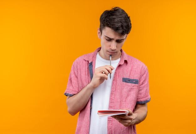 Denkende blanke jonge kerel die de roze pen en het notitieboekje van de overhemdsholding op geïsoleerde oranje muur draagt