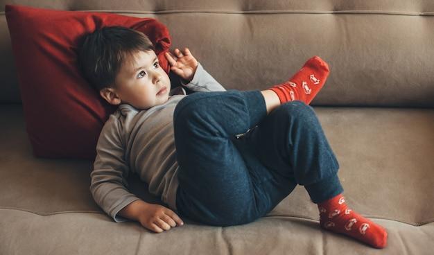 Denkende blanke jongen liggend op de bank met een rood kussen wegkijken in een zonnige dag