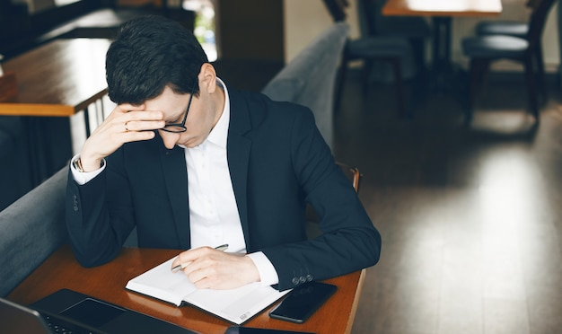 Denkende blanke zakenman probeert iets te schrijven tijdens het wachten op een telefoontje