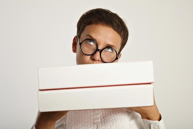 Denkende brunette met ronde bril houdt grote mappen voor haar met een nieuw onderwijsplan voor volgend jaar op de universiteit