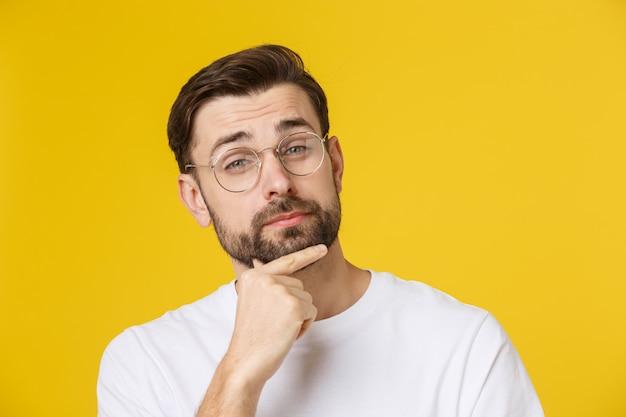 Denkende die mens op geel wordt geïsoleerd. close-upportret van een toevallige jonge peinzende mens die omhoog copyspace bekijken. kaukasisch mannelijk model.