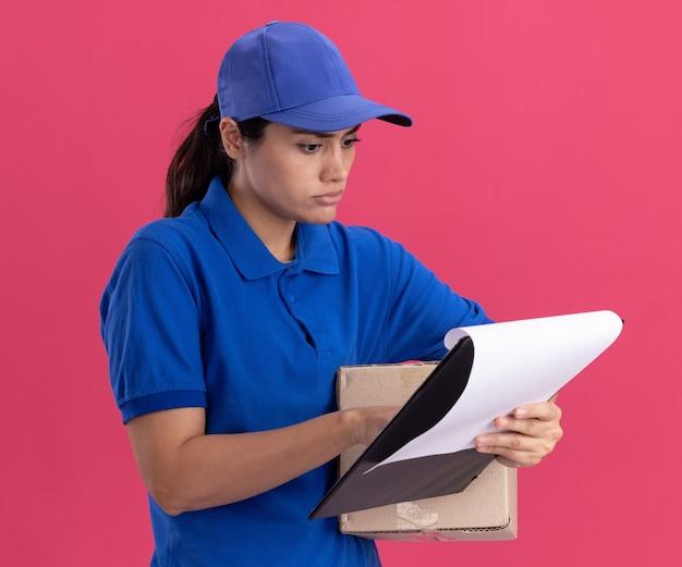 Denkende jong leveringsmeisje die uniform met de doos van de glbholding dragen en klembord in haar hand bekijken dat op roze muur wordt geïsoleerd