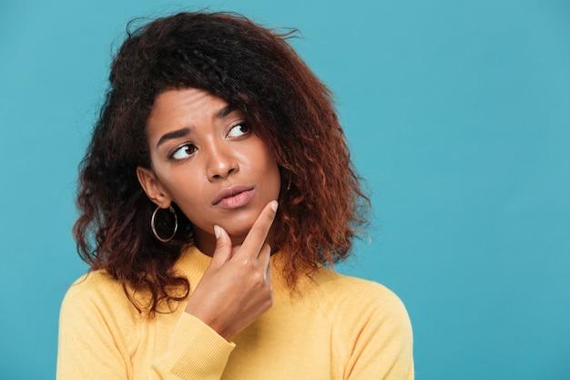 Denkende jonge afrikaanse dame gekleed in warme sweater