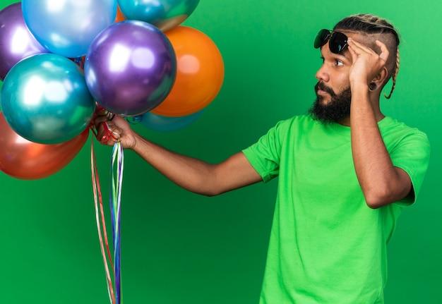 Denkende jonge afro-amerikaanse man met een bril die ballonnen vasthoudt en bekijkt