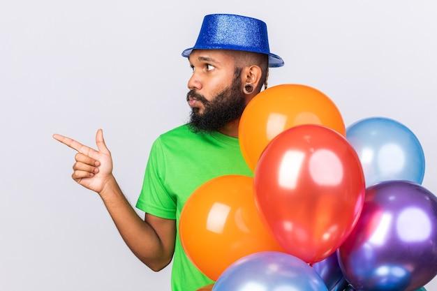 Denkende jonge afro-amerikaanse man met een feestmuts die achter ballonnen staat, wijst aan de zijkant