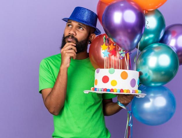 Denkende jonge afro-amerikaanse man met feestmuts die ballonnen vasthoudt met cake, greep kin geïsoleerd op blauwe muur