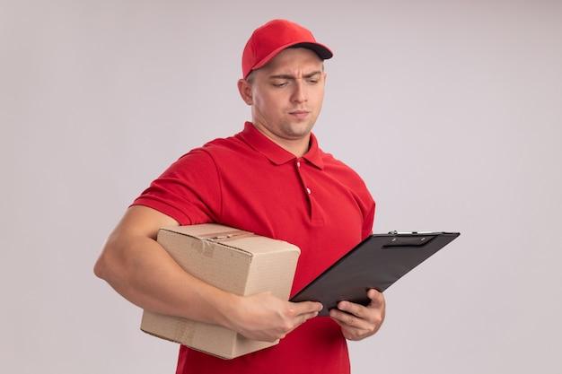 Denkende jonge bezorger die een uniform draagt met een dop die een doos vasthoudt en naar een klembord in zijn hand kijkt, geïsoleerd op een witte muur