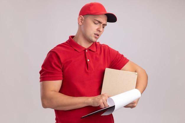 Denkende jonge bezorger die uniform met de doos van de glbholding draagt en naar klembord in zijn hand kijkt die op witte muur wordt geïsoleerd