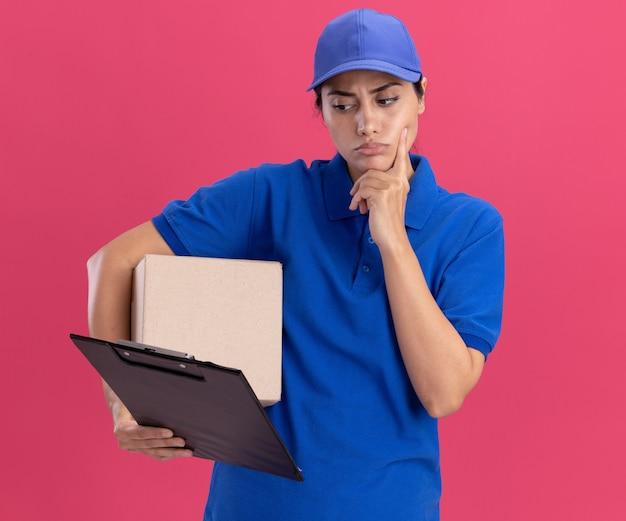 Denkende jonge bezorger die uniform met pet draagt ?? die doos houdt en naar klembord in haar hand kijkt die vinger op wang legt die op roze muur wordt geïsoleerd