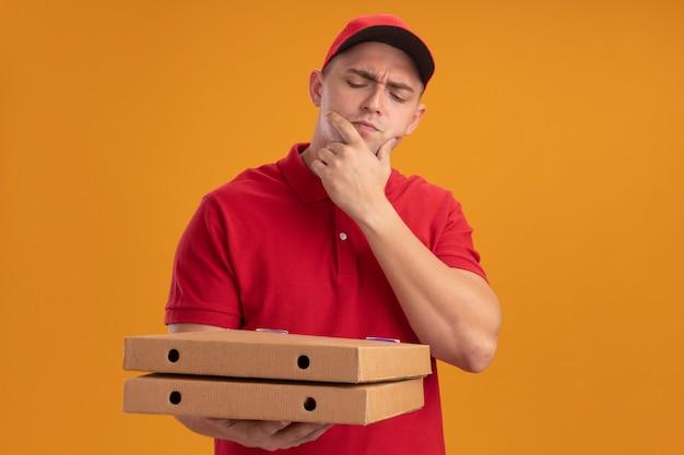 Denkende jonge bezorger die uniform met pet draagt en pizzadozen bekijkt die hand op kin zetten die op oranje muur wordt geïsoleerd