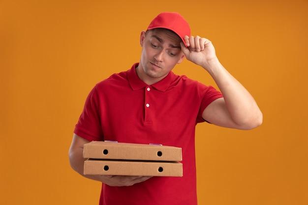 Denkende jonge bezorger die uniform met pet draagt en pizzadozen bekijkt die op oranje muur worden geïsoleerd