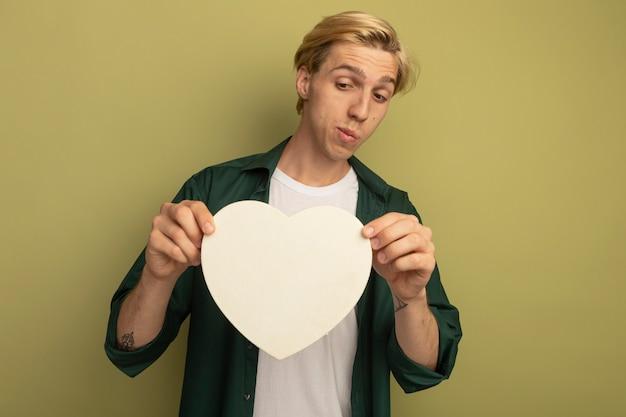 Denkende jonge blonde kerel die groene t-shirt draagt ?? die en de doos van de hartvorm bekijkt bekijkt