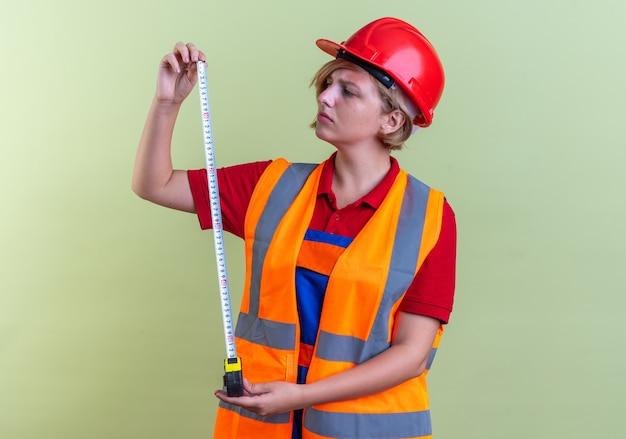 Denkende jonge bouwvrouw in uniform die zich meetlint uitstrekt geïsoleerd op olijfgroene muur