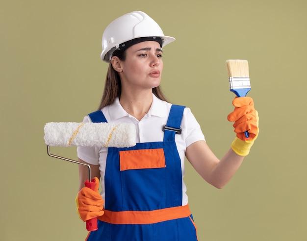 Denkende jonge bouwvrouw in uniform en handschoenen met rolborstel en kijken naar verfborstel in haar hand geïsoleerd op olijfgroene muur