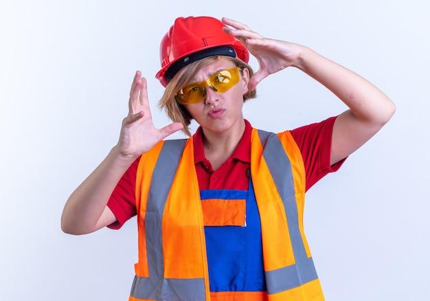 Denkende jonge bouwvrouw in uniform met een bril die een fotogebaar toont dat op een witte achtergrond wordt geïsoleerd