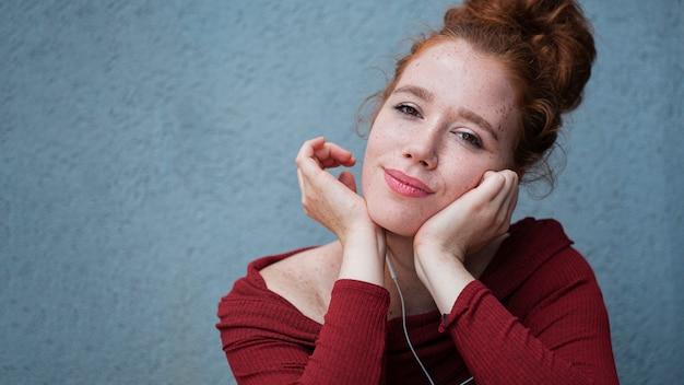 Denkende jonge dame die naar muziek luistert