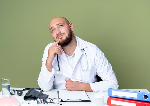 Denkende jonge kale mannelijke arts die medische robe en stethoscoopzitting bij bureau draagt