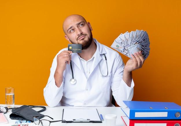 Denkende jonge kale mannelijke arts met een medisch gewaad en een stethoscoop die aan het bureau zit