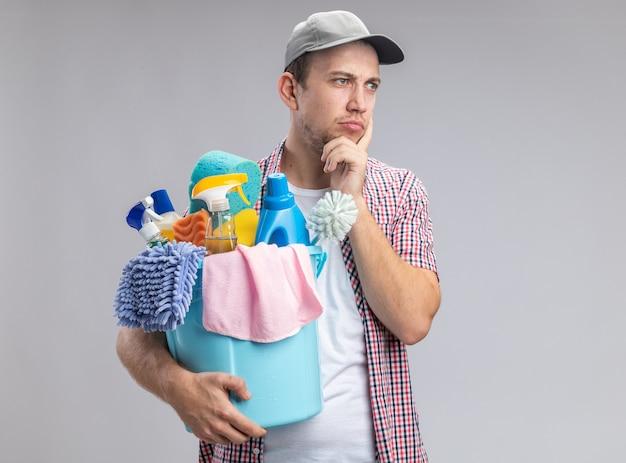 Denkende jonge kerel schoner met pet met emmer met schoonmaakgereedschap die vinger op de wang zet geïsoleerd op een witte achtergrond