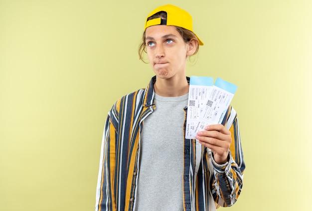 Denkende jonge kerel student draagt rugzak met pet met kaartjes geïsoleerd op olijfgroene muur