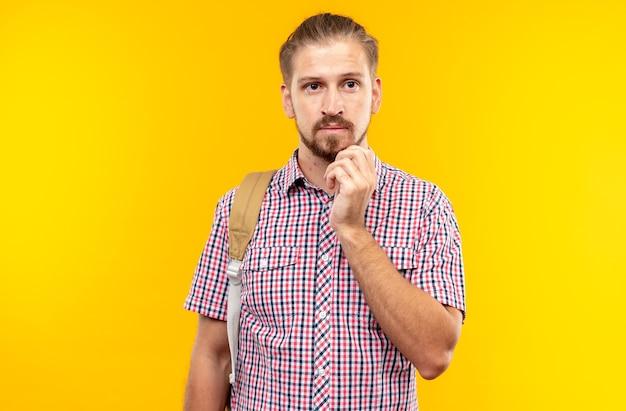 Denkende jonge kerelstudent die rugzak draagt die hand op kin legt
